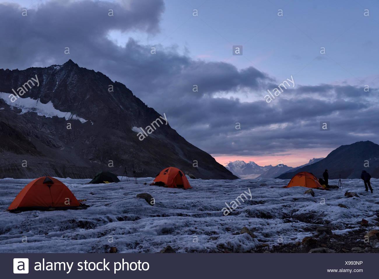 Il team italiano di grotta esploratori sistemarvi in serata presso il loro campo base sul Aletschgletscher. Crepuscolo caldo illumina il tende di colore arancione Immagini Stock
