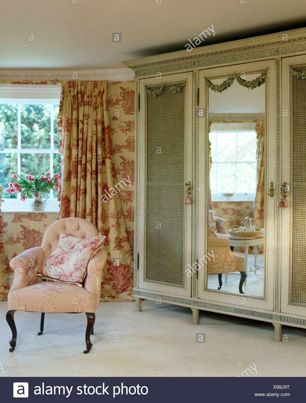 Poltrona rosa accanto all antico armadio con porta in ...