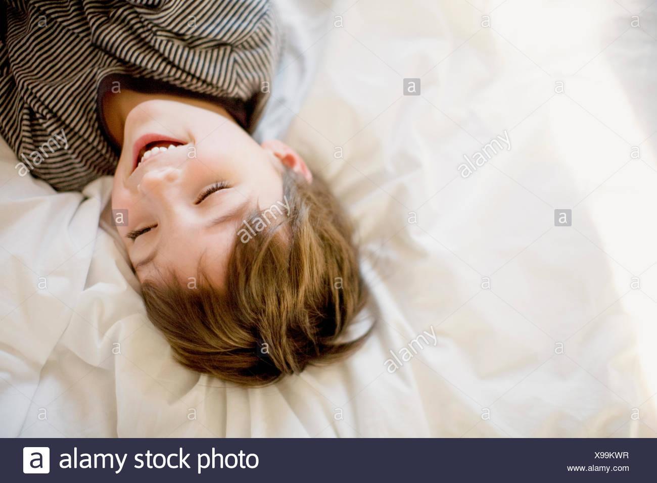 Felice ragazzo disteso sul letto Immagini Stock