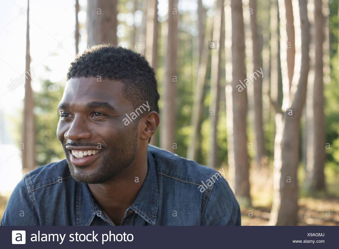 Un Uomo in camicia blu all'ombra degli alberi Immagini Stock