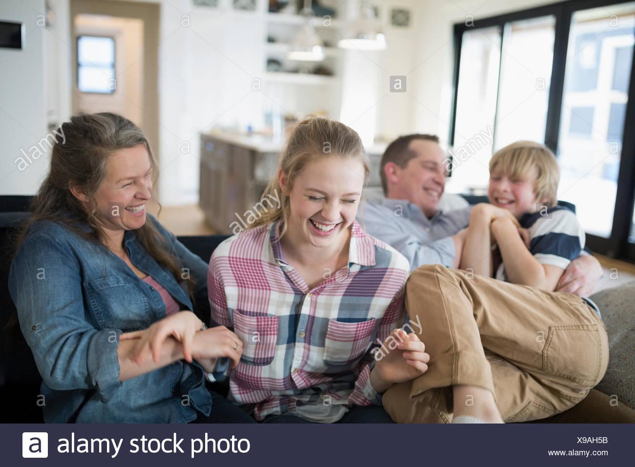 Ridere la famiglia sul divano Immagini Stock