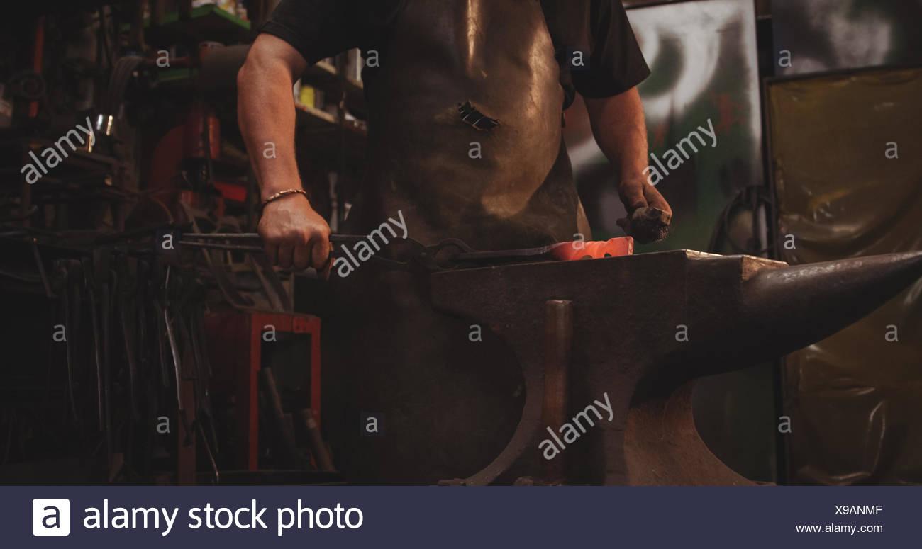 Fabbro lavora su metallo caldo utilizzando un martello a forma Immagini Stock