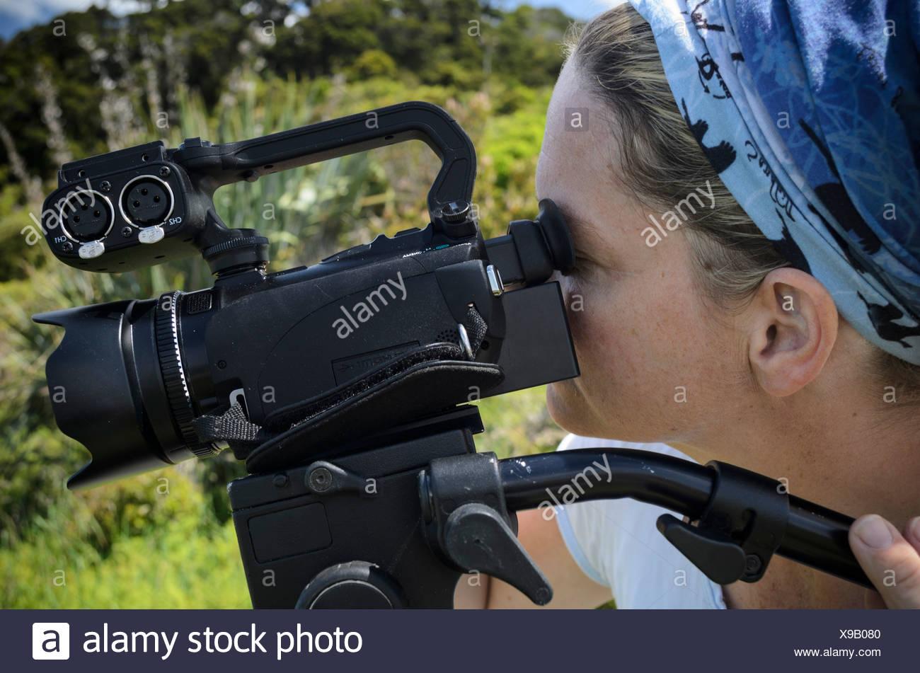 Giovane donna che guarda attraverso il mirino di un video HD fotocamera su un treppiede, Nuova Zelanda, Oceania Immagini Stock