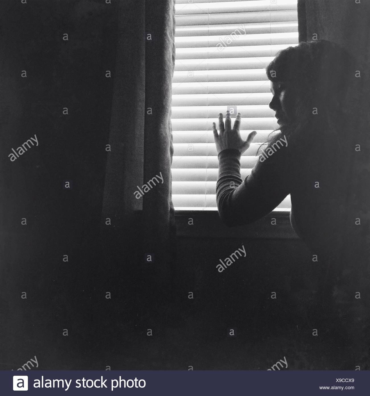 Giovane donna in piedi contro la finestra a casa Immagini Stock