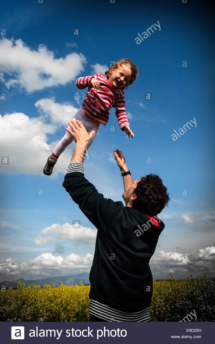 Padre nel lanciare la sua figlia (4-5) nel prato di fiori Immagini Stock