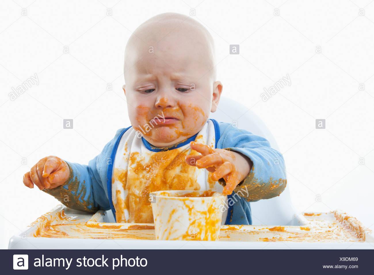 Baby boy (6- 11 mesi) con cibo per neonati e pianto Immagini Stock