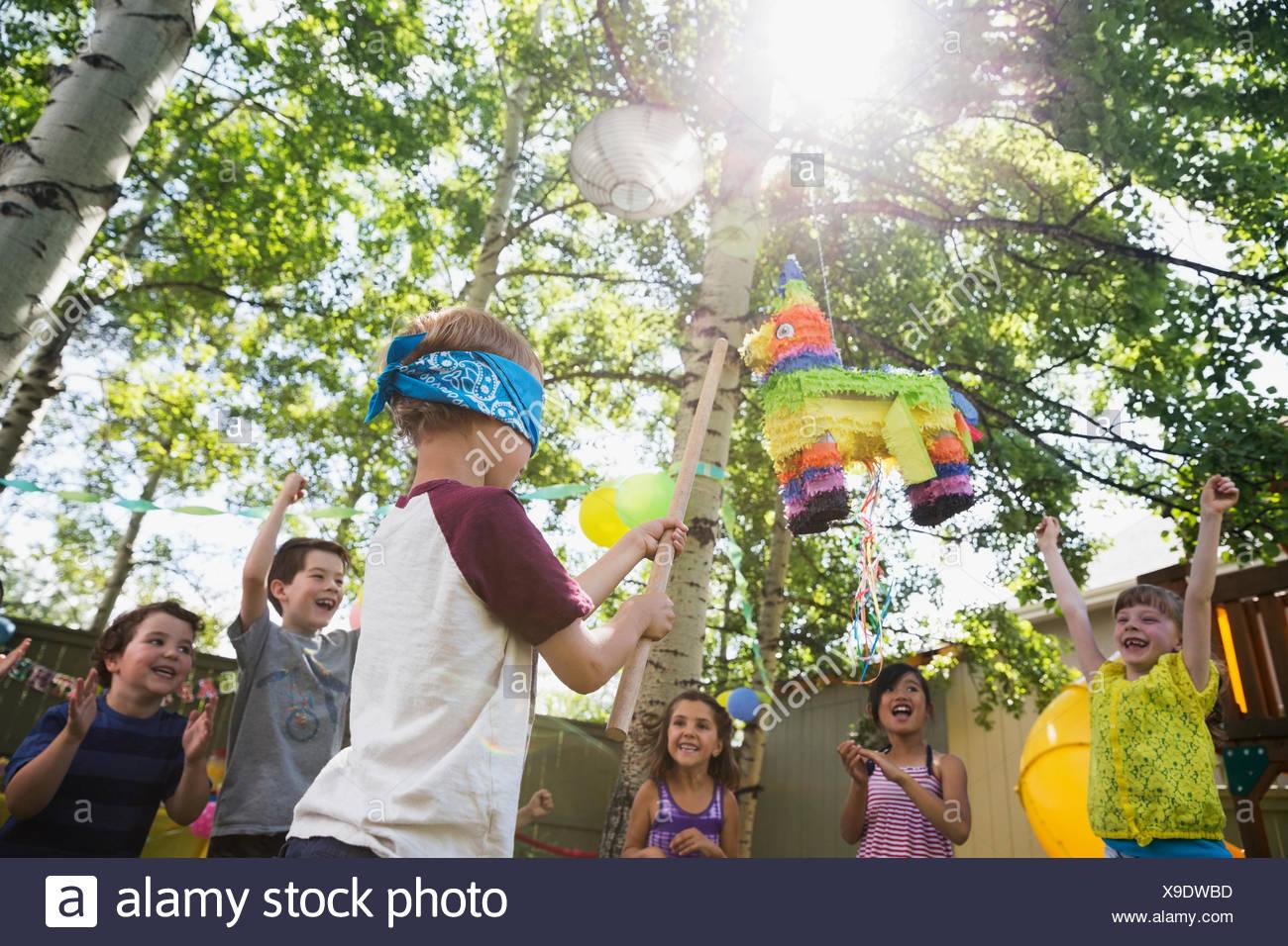 Bambini il tifo per gli occhi bendati boy swinging a pinata Immagini Stock