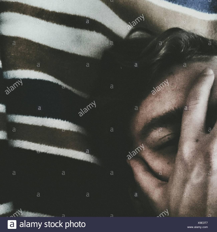 Immagine ritagliata dell uomo che copre il volto mentre vi rilassate sul letto Immagini Stock