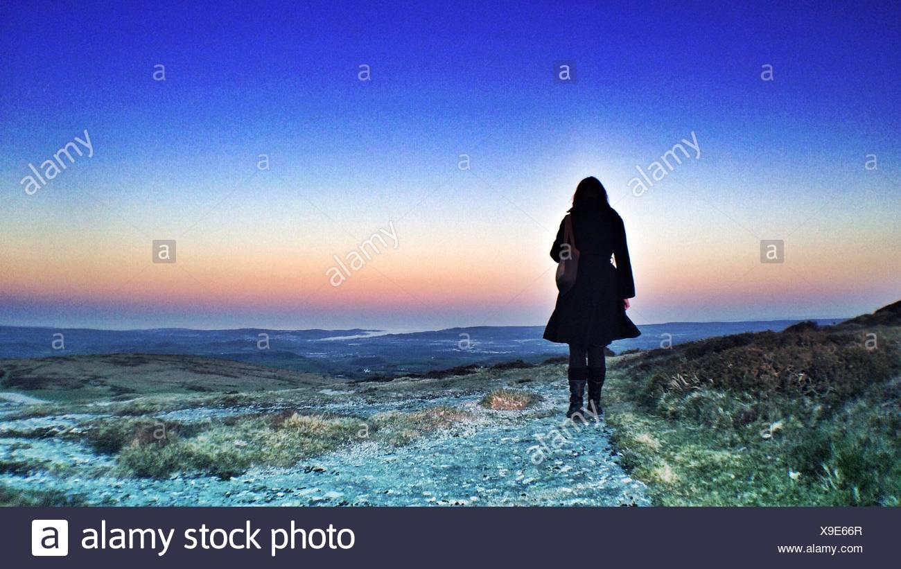 Vista posteriore della donna in piedi contro il cielo drammatico Immagini Stock