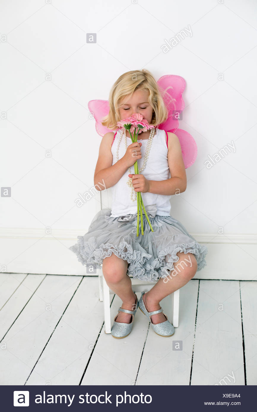 Giovane ragazza in posa per una foto in un studio di fotografi, tenendo in mano un mazzo di fiori. Immagini Stock