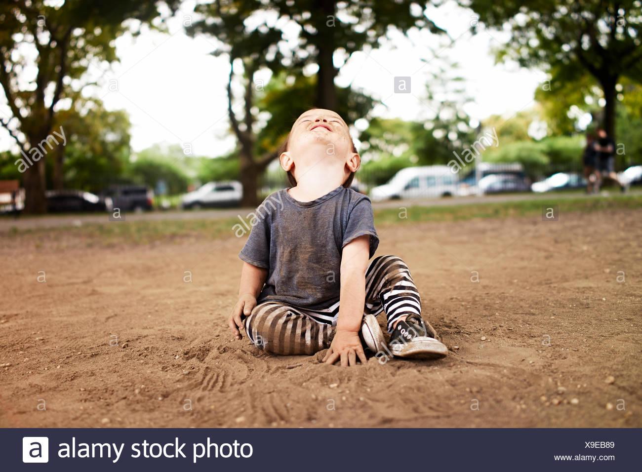 Bimbi maschio in seduta park cercando Immagini Stock