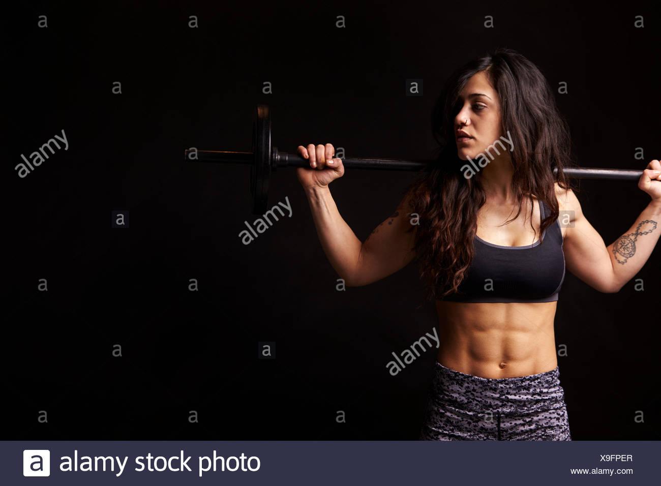 Muscoloso dai capelli scuri donna holding barbell sulle sue spalle Immagini Stock