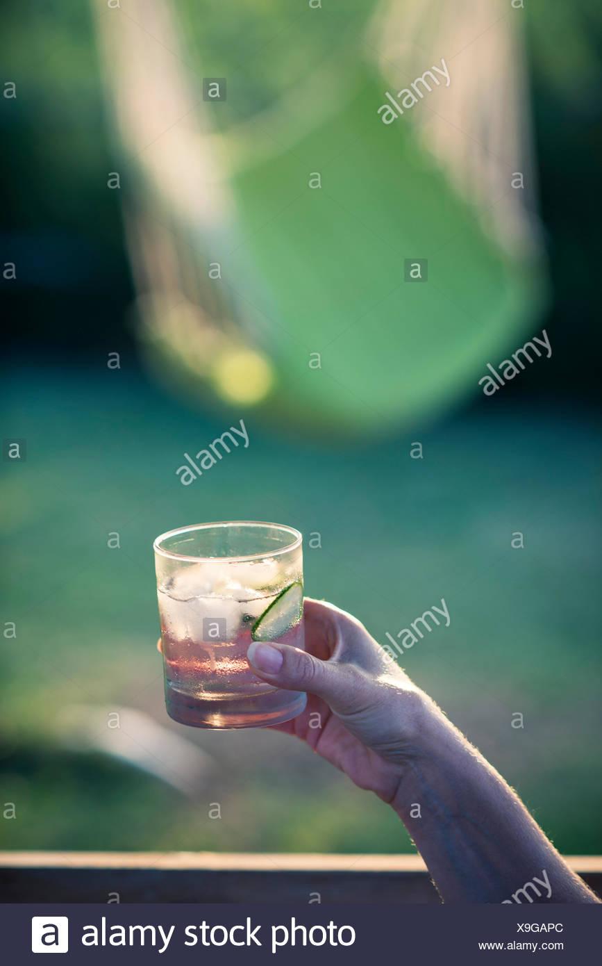 Il gin tonic in mano nella luce della sera Immagini Stock