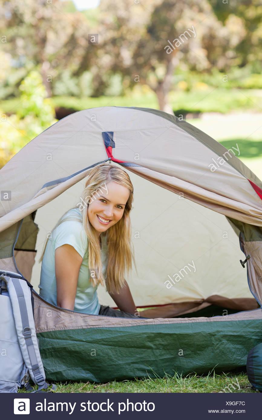 Una donna seduta nella tenda sorridente con la sua testa appena al di fuori della porta Immagini Stock