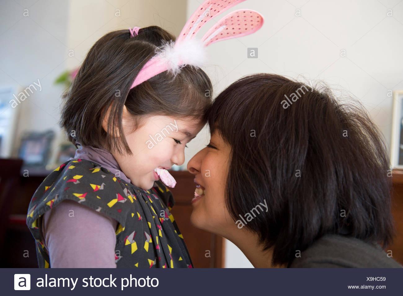 Madre e figlia, faccia a faccia, figlia indossando orecchie di coniglietto e tenendo il dolce in bocca Immagini Stock