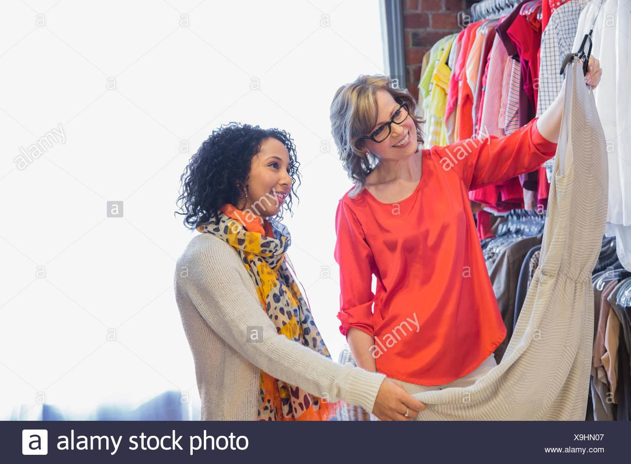 Femmina proprietario di piccola impresa ad assistere il cliente con la scelta di abbigliamento Immagini Stock