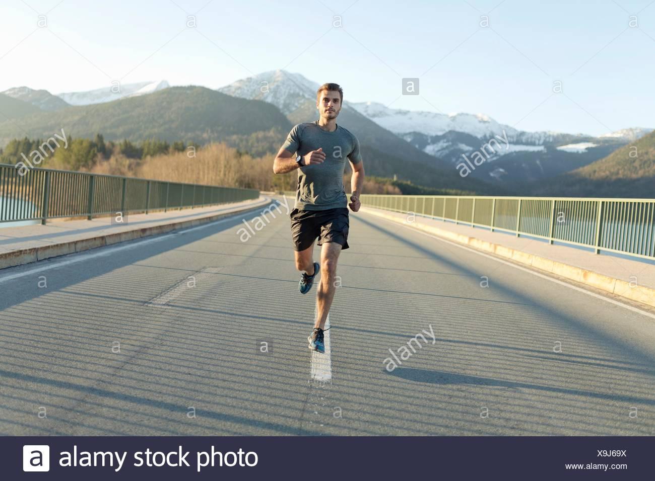 Giovane uomo, in esecuzione su strada, montagne dietro di lui, vista frontale Immagini Stock