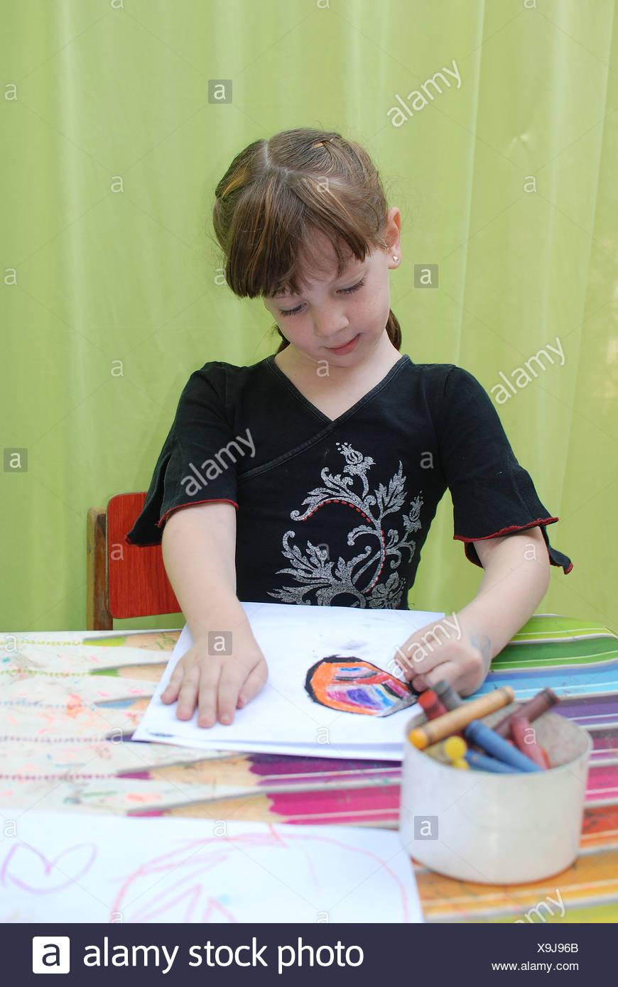 Ragazza in età prescolare di 5 divertente se stessa durante il disegno Immagini Stock