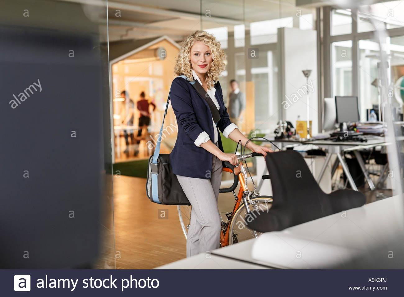 Ritratto di donna con la bicicletta in ufficio Immagini Stock