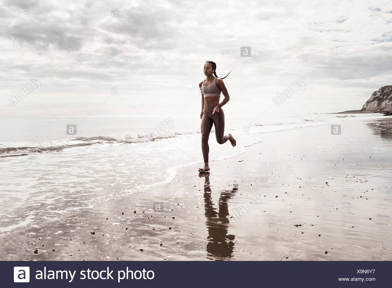 Giovani femmine runner correre a piedi nudi lungo il bordo d'acqua a beach Immagini Stock