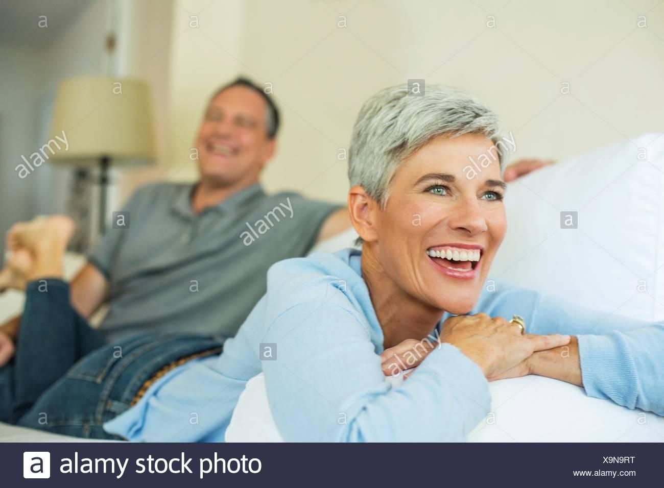 Coppia matura ridendo e rilassante sul divano Immagini Stock
