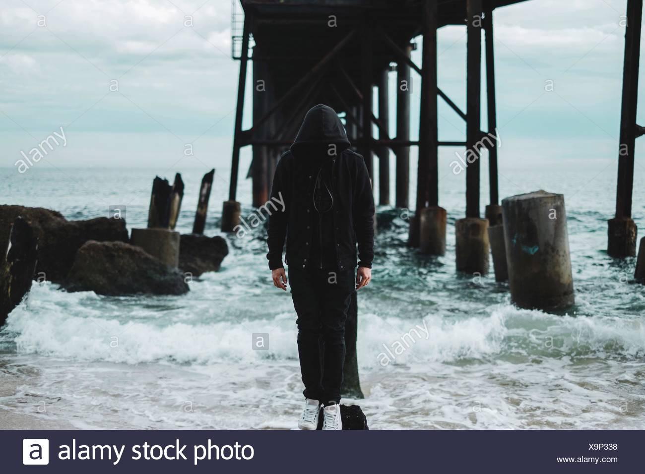 Misterioso uomo in piedi sulla roccia in mare Immagini Stock