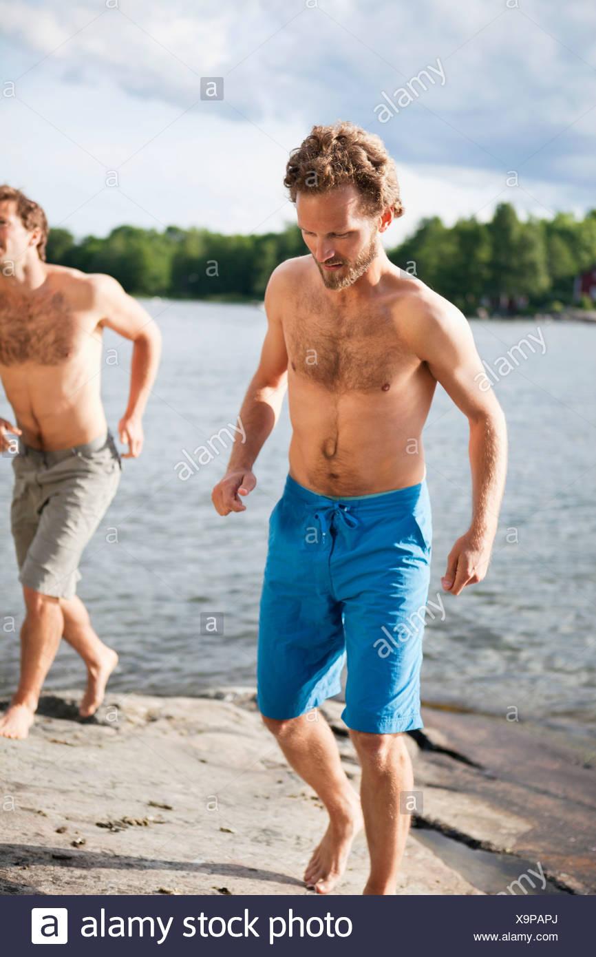 Gli uomini nella spiaggia di usura Immagini Stock