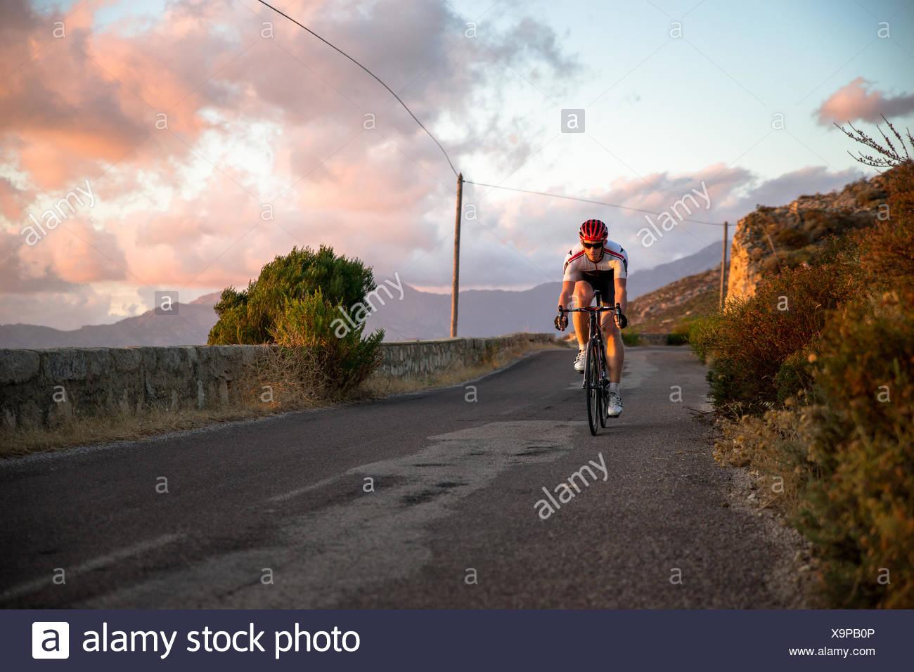 Francia, Corsica, il ciclismo su strada al di sopra di mare al tramonto Immagini Stock