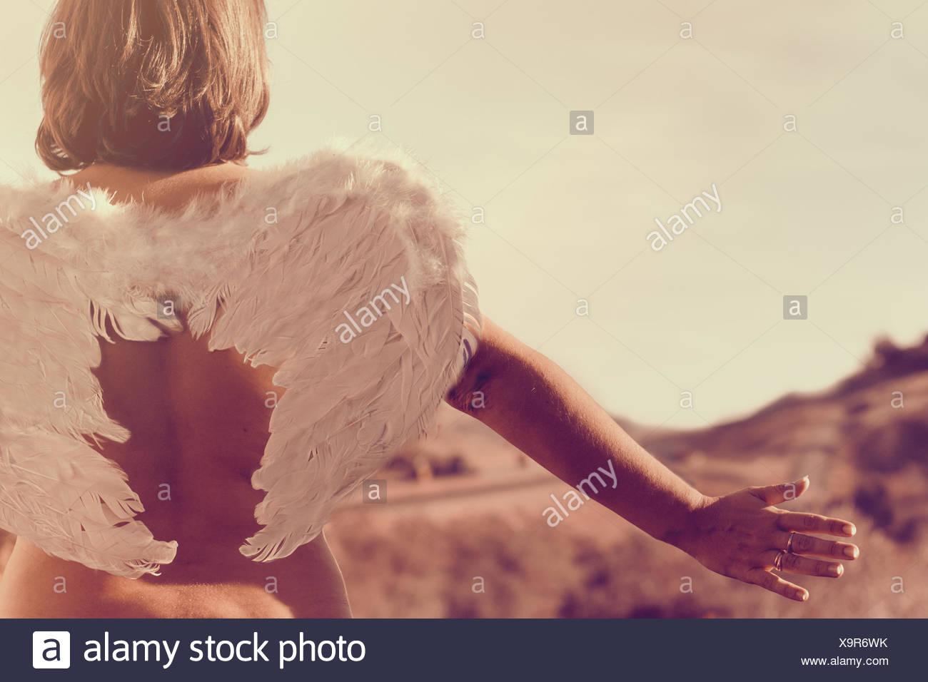 Vista posteriore di una donna che indossa un paio di ali d'angelo con le braccia tese Foto Stock