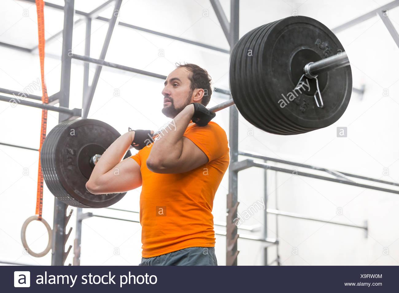 Fiducioso l uomo che guarda lontano mentre il sollevamento barbell in palestra crossfit Immagini Stock