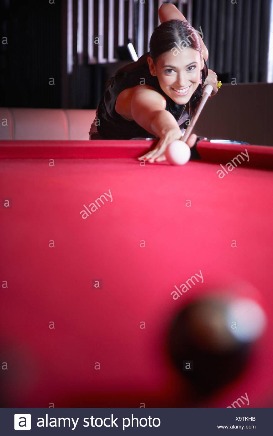 Donna giocando a biliardo e sorridente Immagini Stock