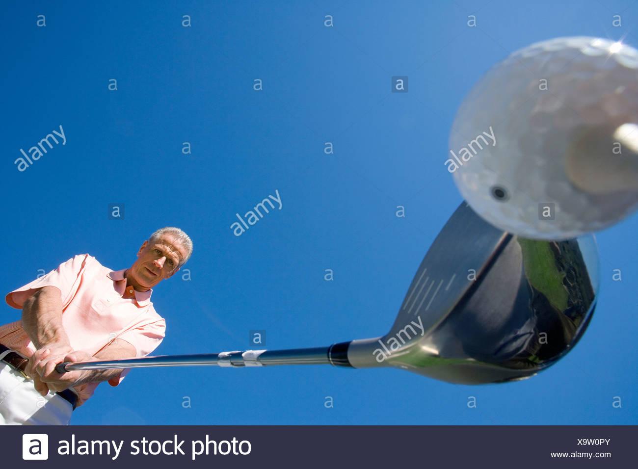 Uomo maturo preparando a tee off sul campo da golf, tenendo driver, close-up, vista verso l'alto angolo largo Immagini Stock