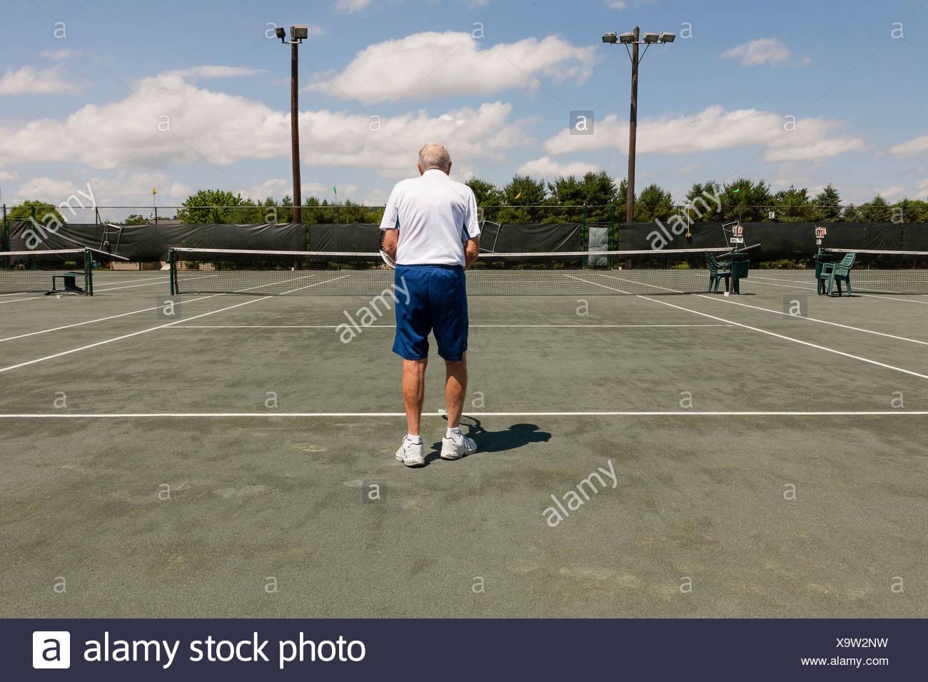 Vista posteriore del senior uomo sul campo da tennis Foto Stock