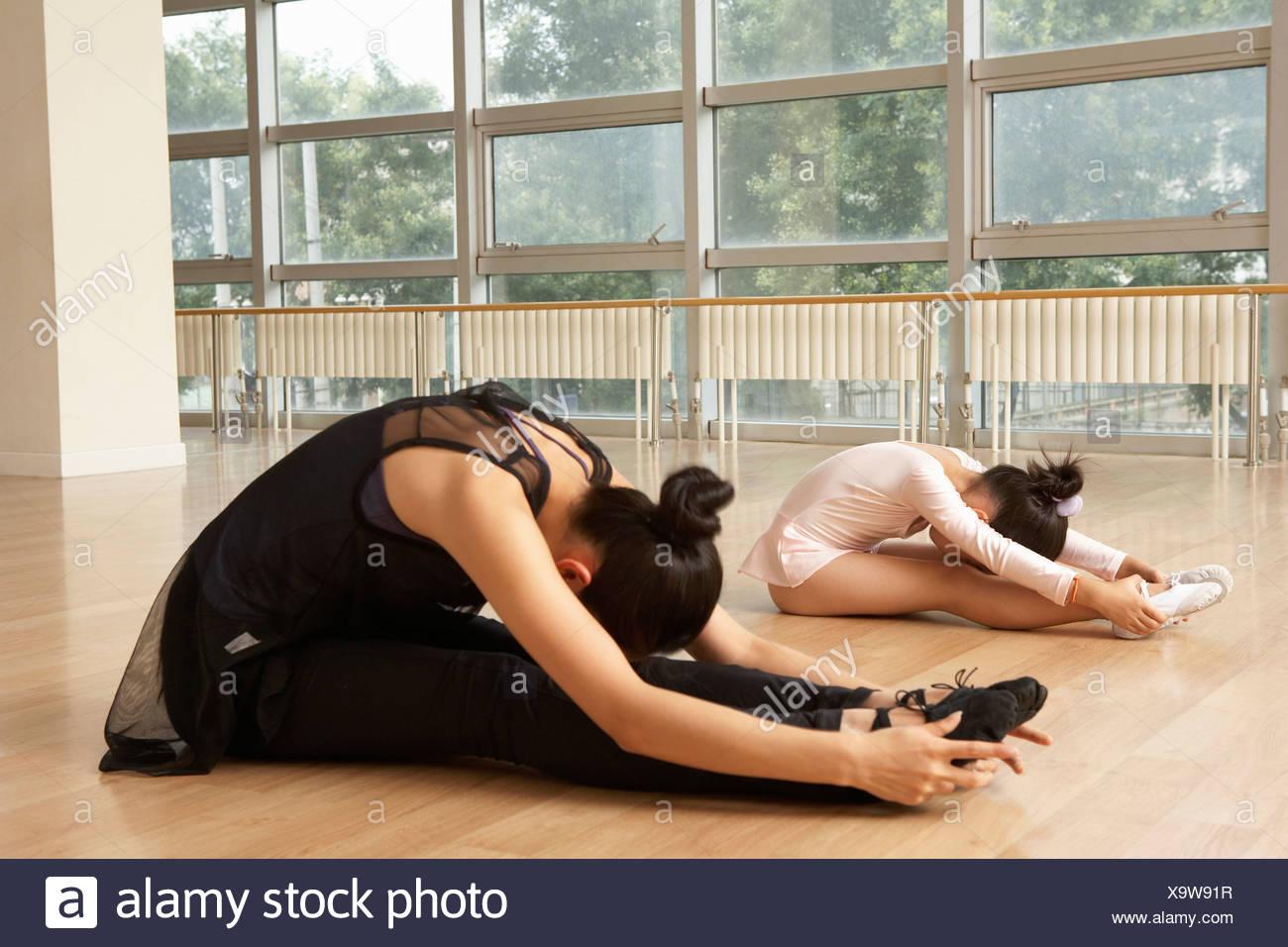 Ballerini Stretching sul pavimento Immagini Stock