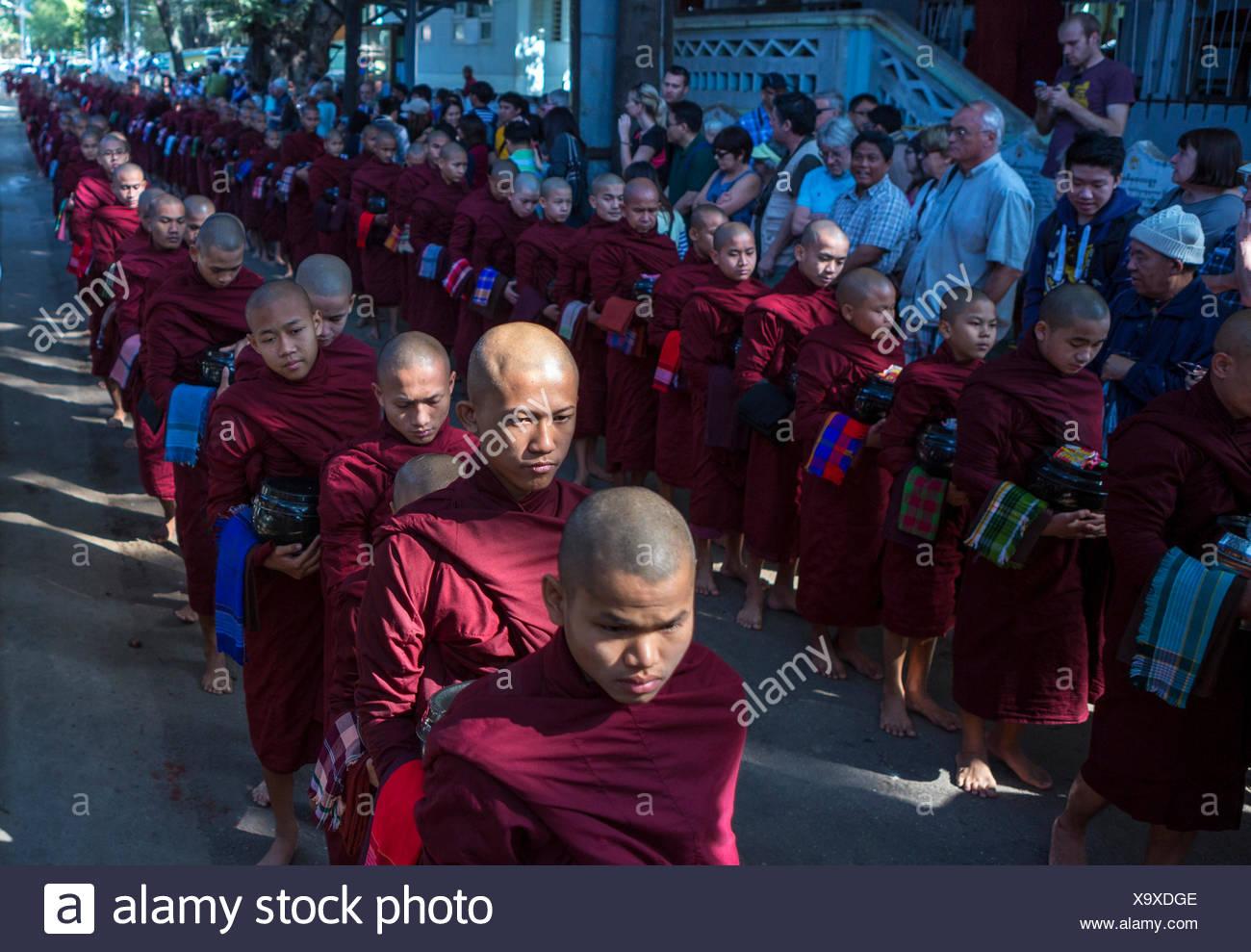 Mandalay MYANMAR Birmania Asia Parade attrazione cue distribuendo cibo monastero monaci pregare la religione ai turisti la tradizione Immagini Stock
