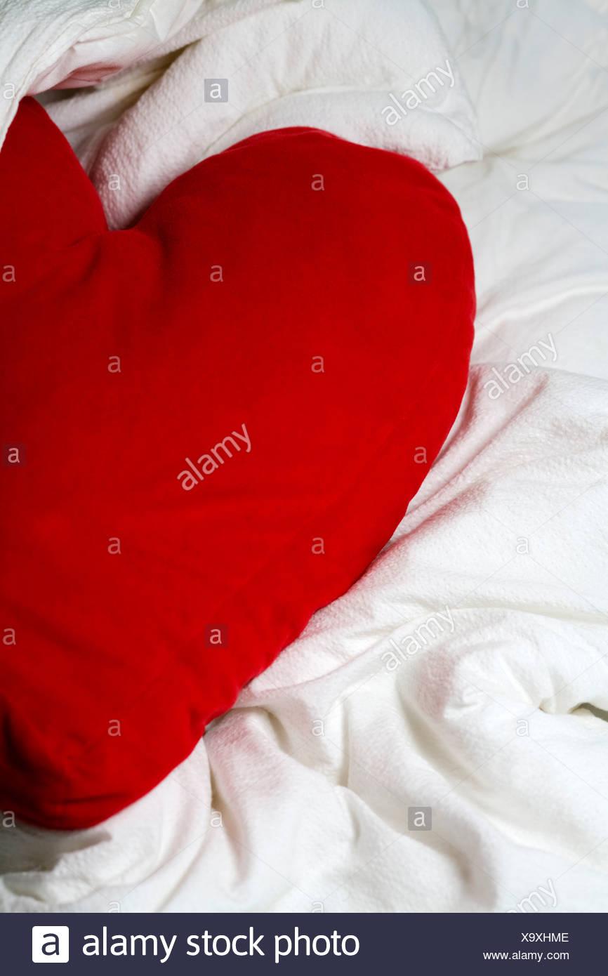 Close-up di un rosso a forma di cuore sul cuscino letto disordinato ...