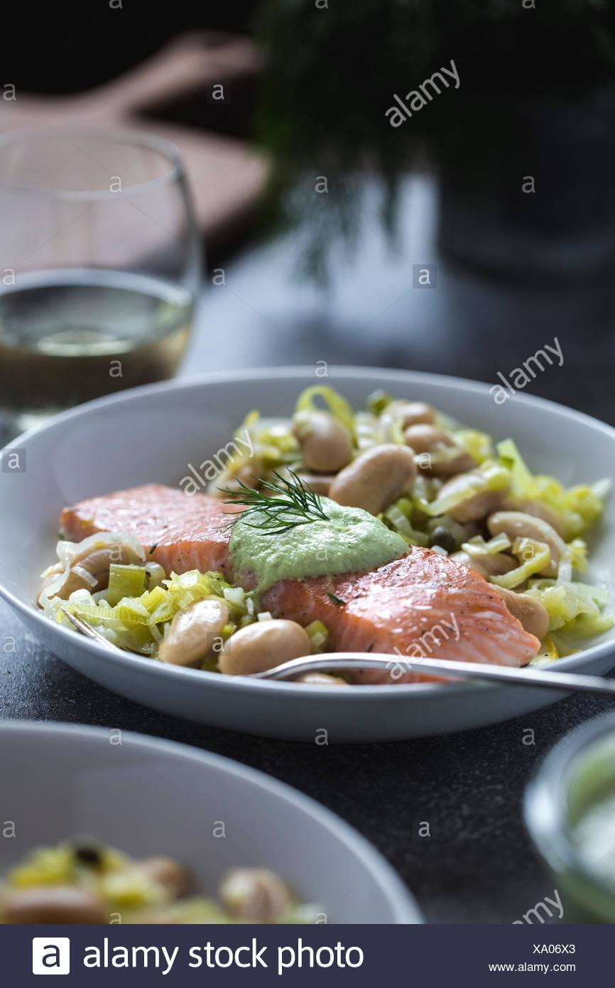 Un piatto pieno di bianco il burro I fagioli conditi con cotta al forno fette di salmone è fotografata dalla vista frontale. Immagini Stock