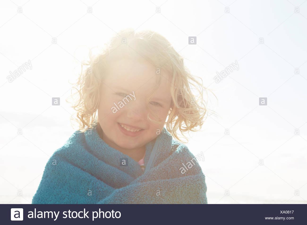 Ritratto di ragazza avvolto in asciugamano a costa soleggiata Immagini Stock