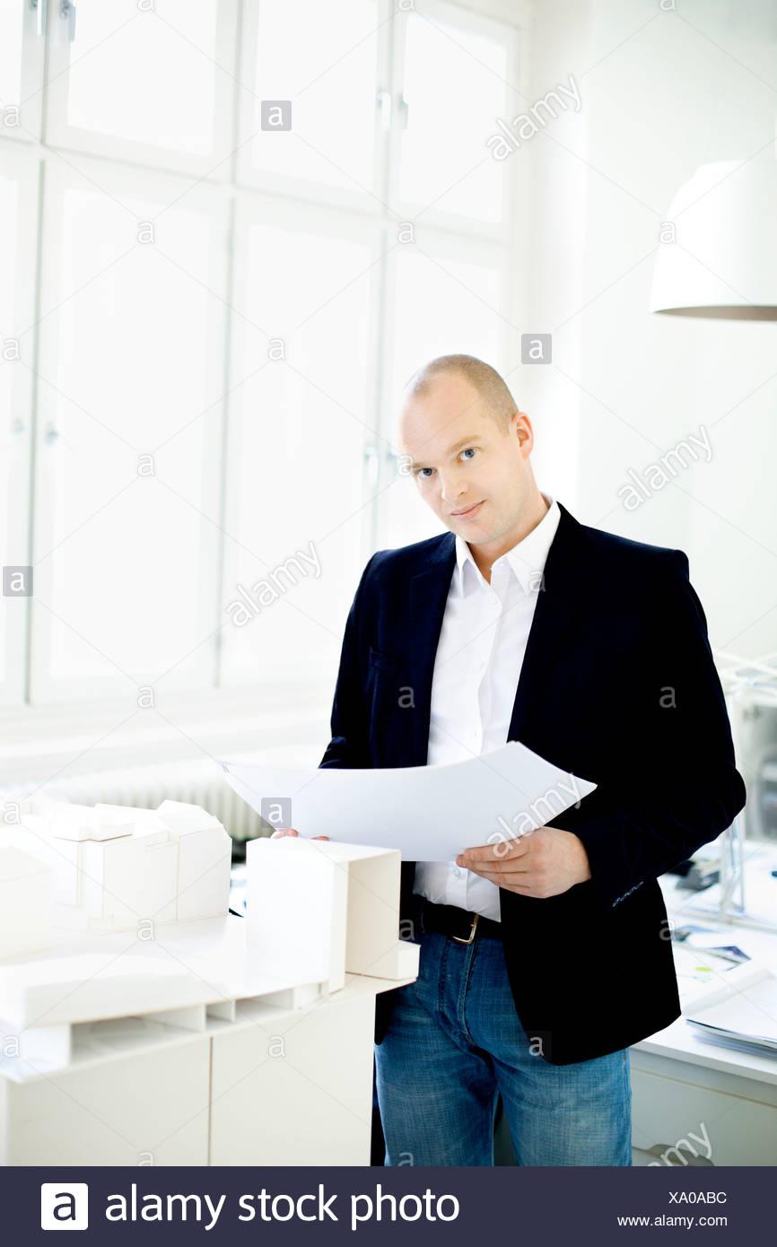 Uomo in piedi dal modello case in ufficio Foto Stock