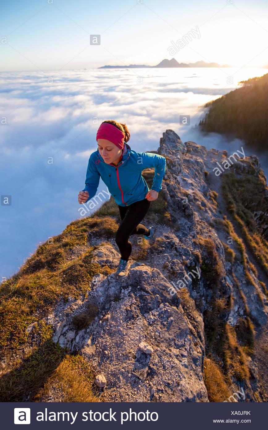 Giovane donna in esecuzione sopra le nuvole, Salisburgo, Austria Immagini Stock