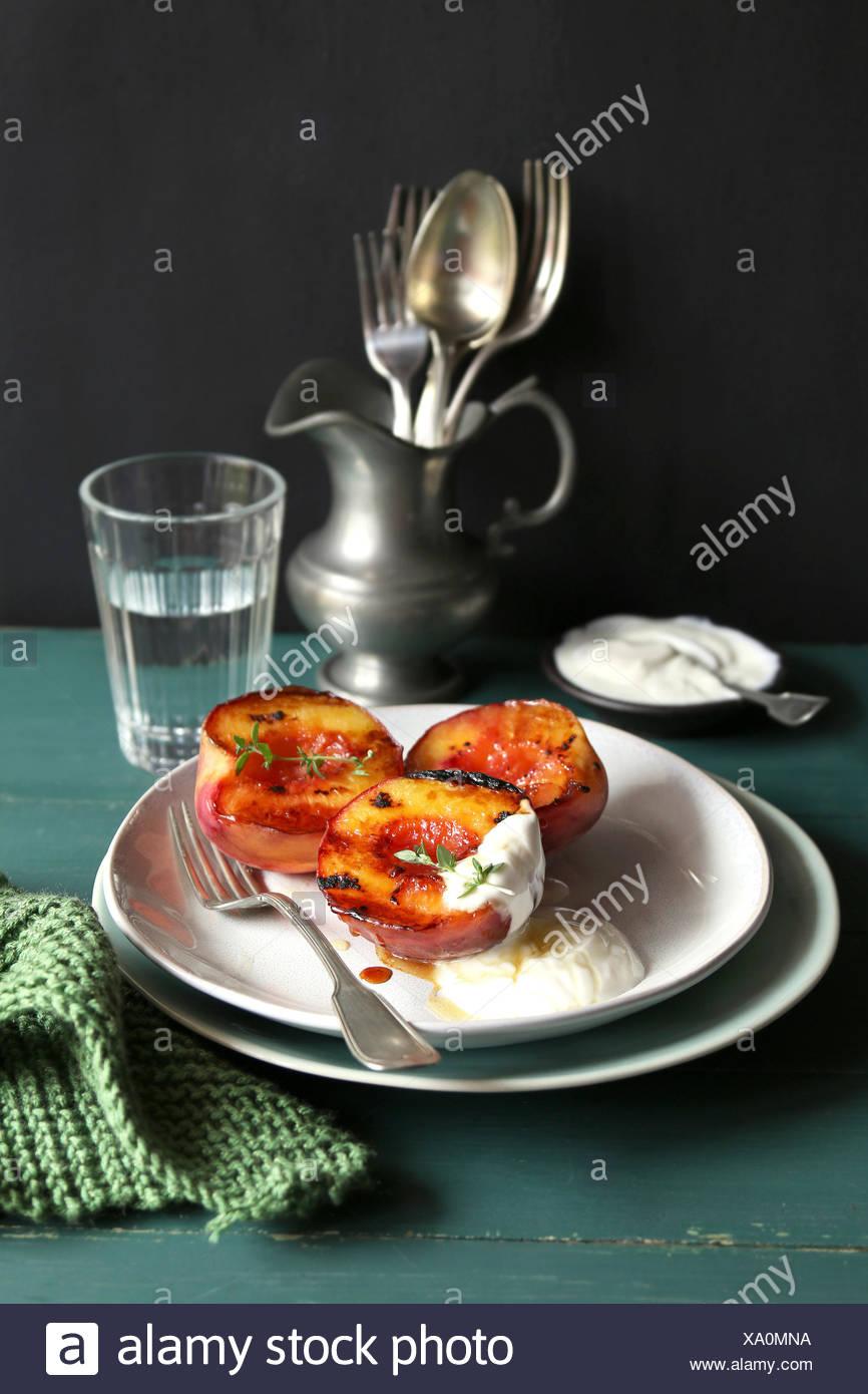 Piastra con grigliate di pesche con lo yogurt greco e miele e decorate con di timo fresco Immagini Stock