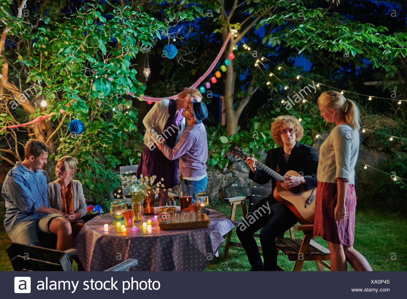 Tre coppie che vogliono godersi la sera party in giardino Immagini Stock