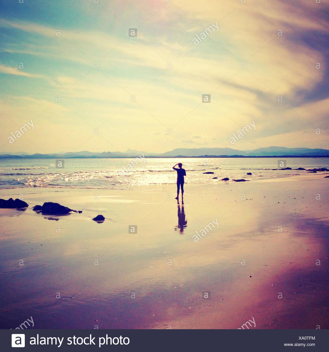 Silhouette di un uomo in piedi sulla spiaggia affacciata sul mare Immagini Stock