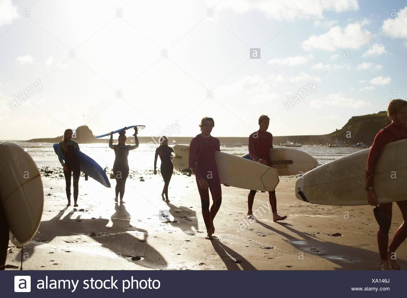 Gruppo di surfers, passeggiate sulla spiaggia, portando le tavole da surf Immagini Stock