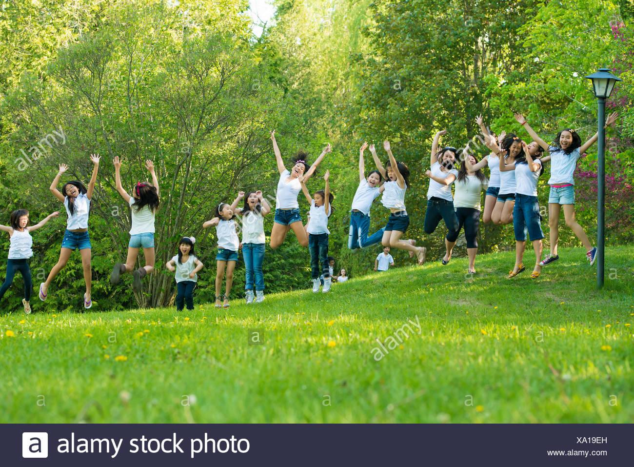 Un folto gruppo di bambini jumping in posizione di parcheggio Immagini Stock