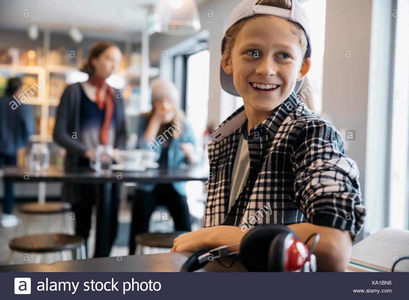 Sorridente Caucasian high school boy studente che sta cercando di distanza in cafe Immagini Stock