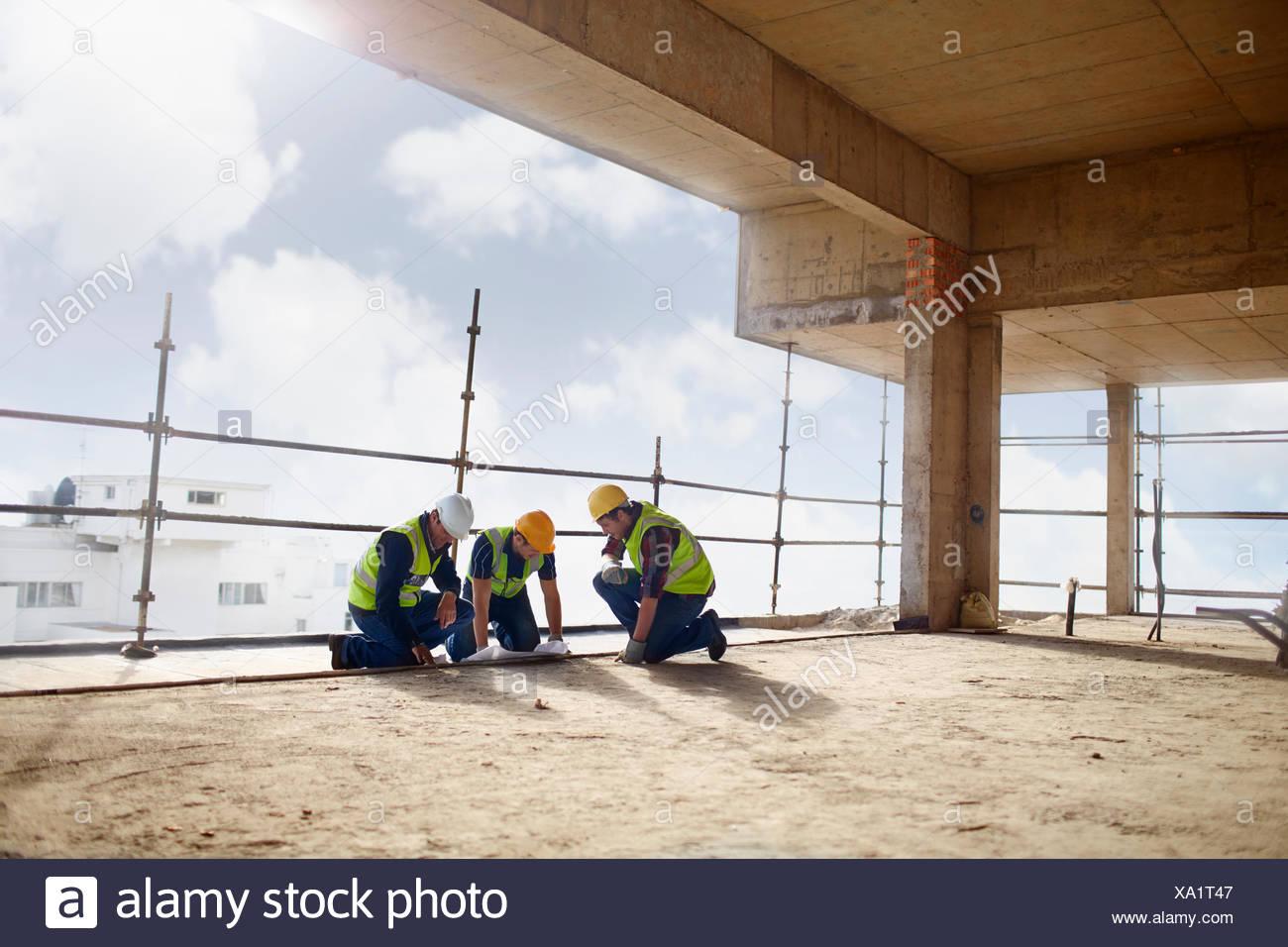 La costruzione dei lavoratori presso il grattacielo sito in costruzione Immagini Stock