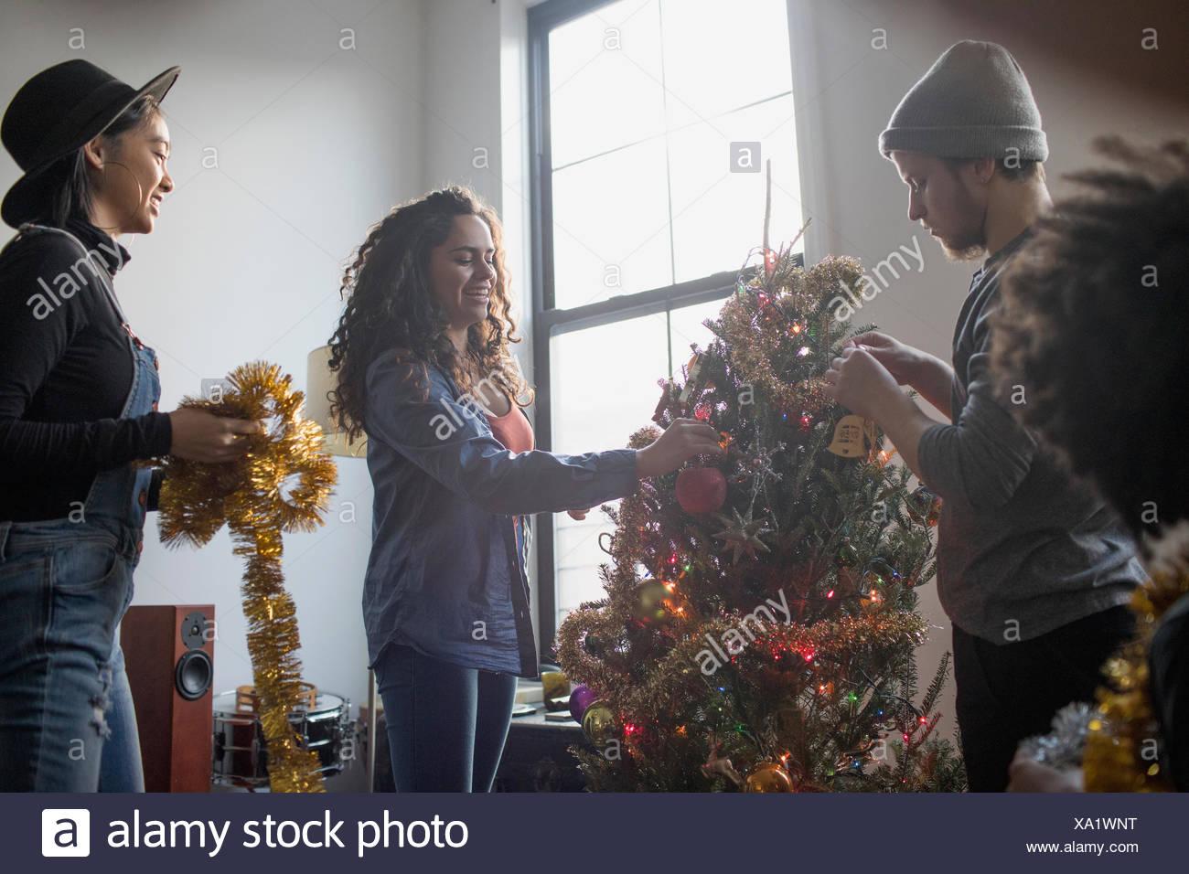 Un gruppo di persone la decorazione di un albero di natale Immagini Stock