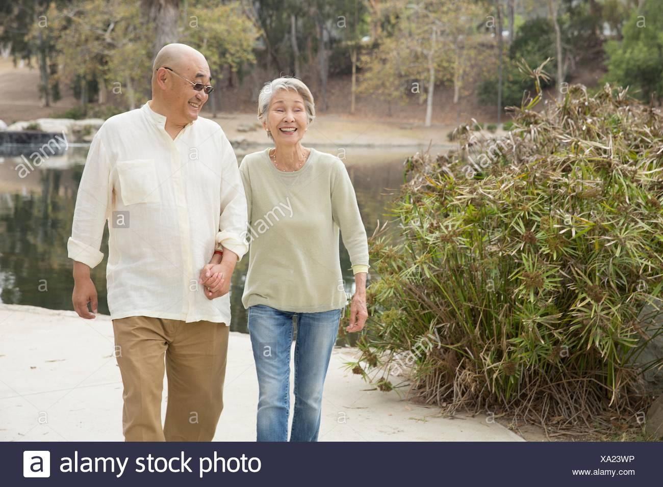 Coppia senior camminando lungo il percorso, tenendo le mani, ridendo Immagini Stock