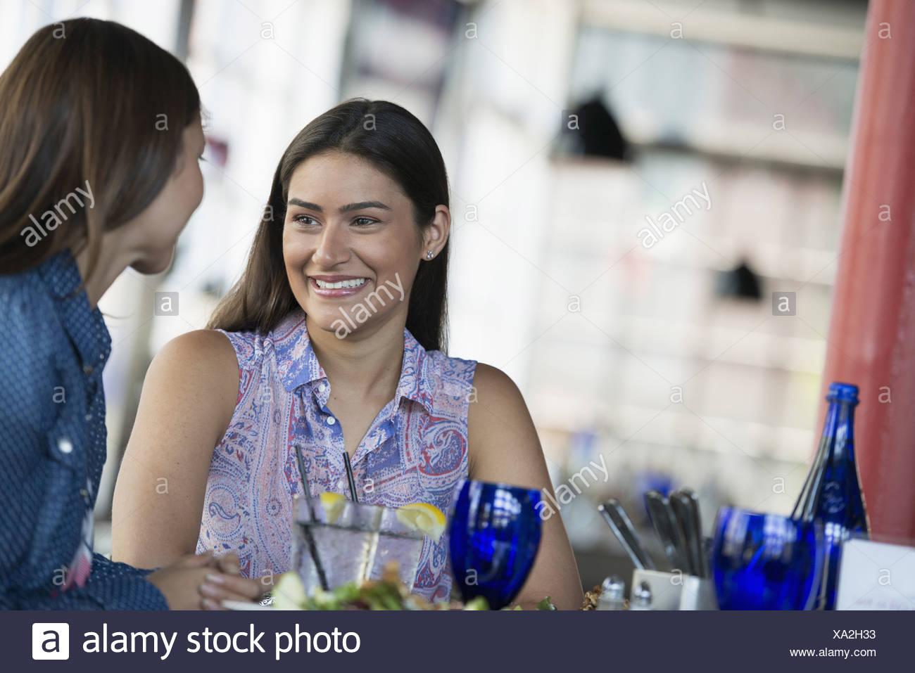 Due donne seduti a un tavolo del bar di consumo di un pasto. Immagini Stock